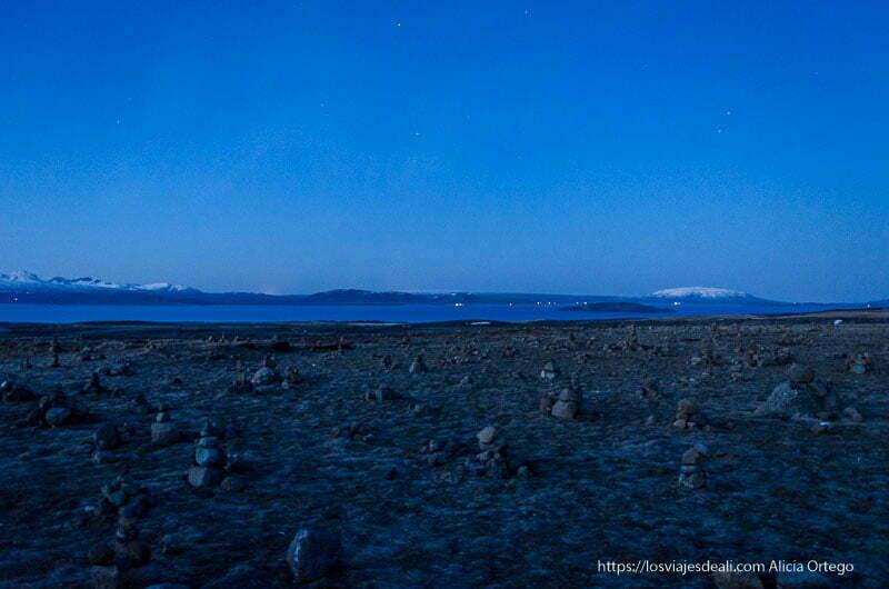 parque de pingvellir por la noche con campo de rocas en primer plano y lago al fondo