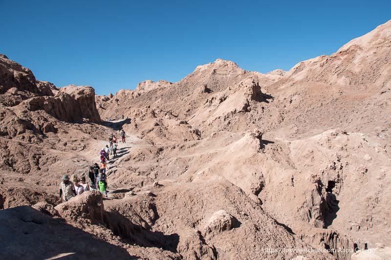 grupo de gente andando por el valle de la luna entre rocas de sal y arena Organizar tu viaje a Chile