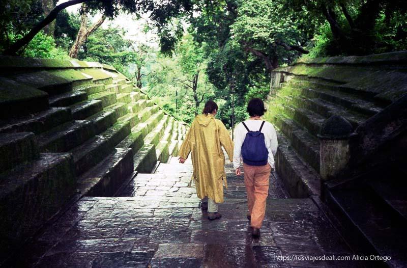 dos turistas bajando por escaleras anchas cubiertas de verdín cerca de katmandu nepal