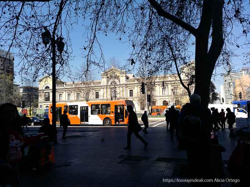 avenida alameda con autobuses naranjas y gente a contraluz