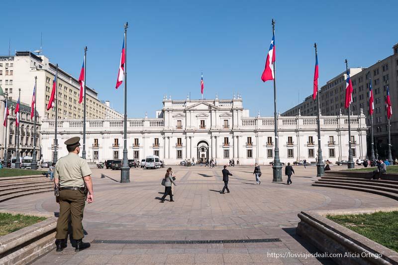 palacio de la moneda de santiago de chile con policía y banderas de chile