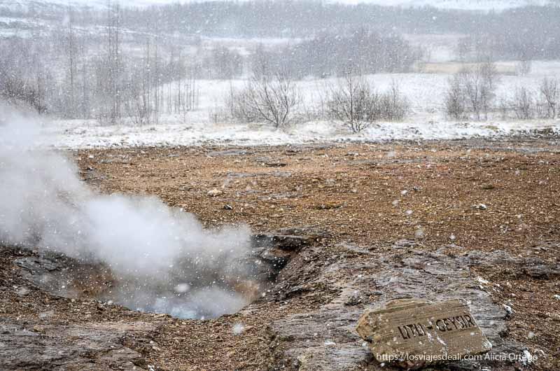 geyser con columna de gases saliendo mientras nievas gruesos copos triángulo dorado de islandia