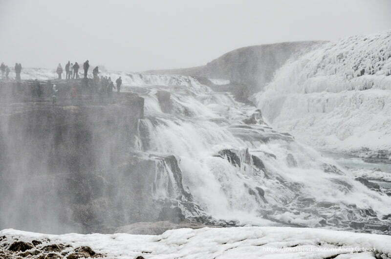 cascada de gulfoss semicongelada con gente asomada al borde apreciándose escala enorme del lugar