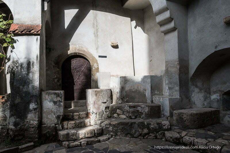 rincón del patio del castillo con escaleras de piedra y pequeña puerta de madera excursión a bran y rasnov