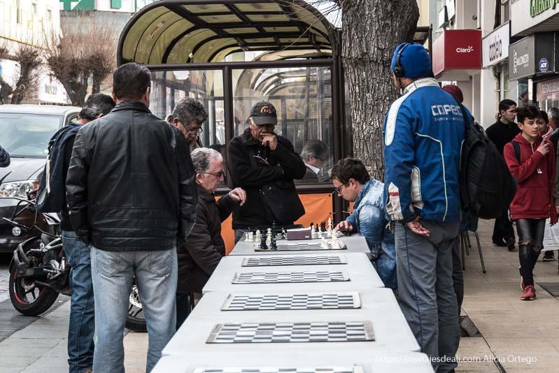 señores jugando al ajedrez en hilera de mesas con tableros y un grupo alrededor mirando atentamente Viña del mar y valparaíso