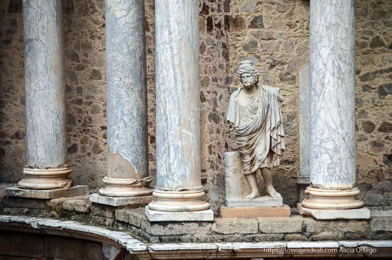 estatua de Zeus de mármol blanco entre las columnas del escenario del anfiteatro romano de mérida