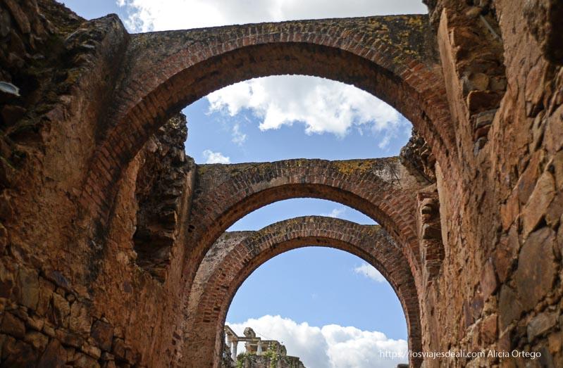 arcos de ladrillo con cielo azul y nubes anfiteatro romano de mérida