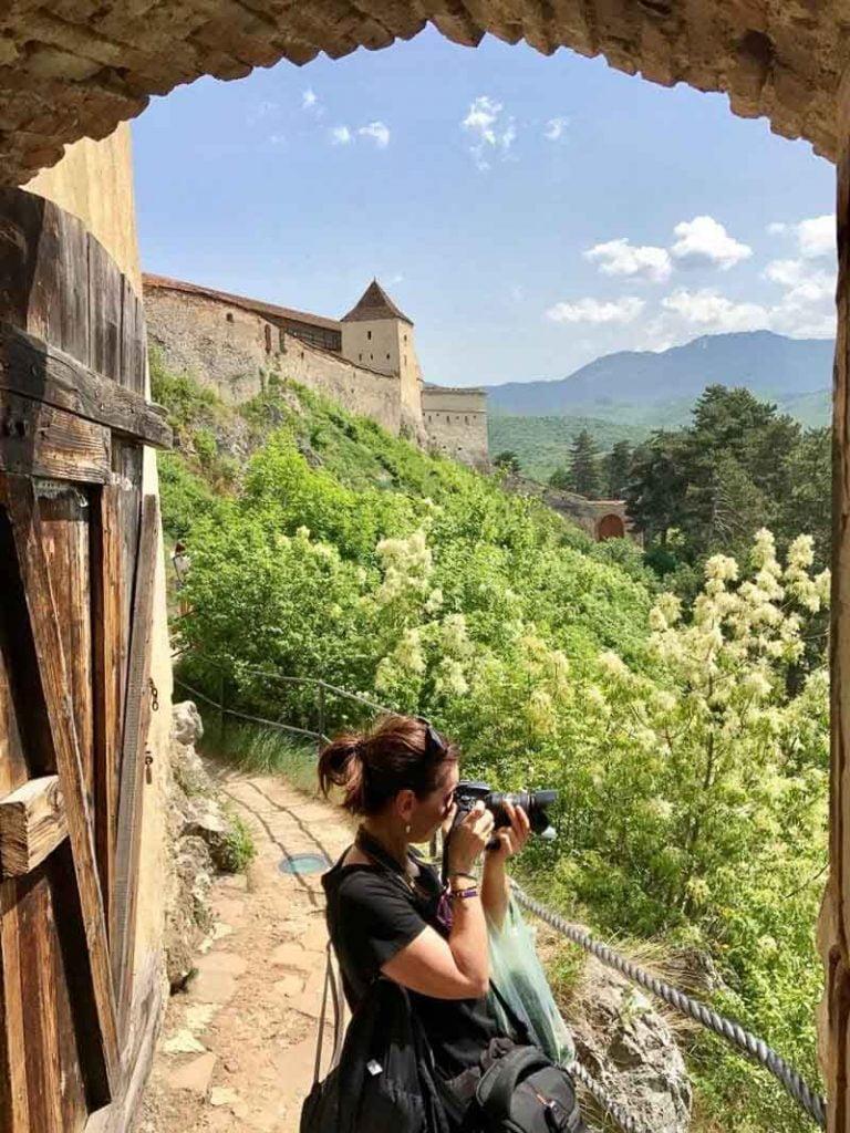yo haciendo fotos bajo la puerta de la ciudadela al fondo parte de la muralla con gran torre cuadrada excursión a bran y rasnov