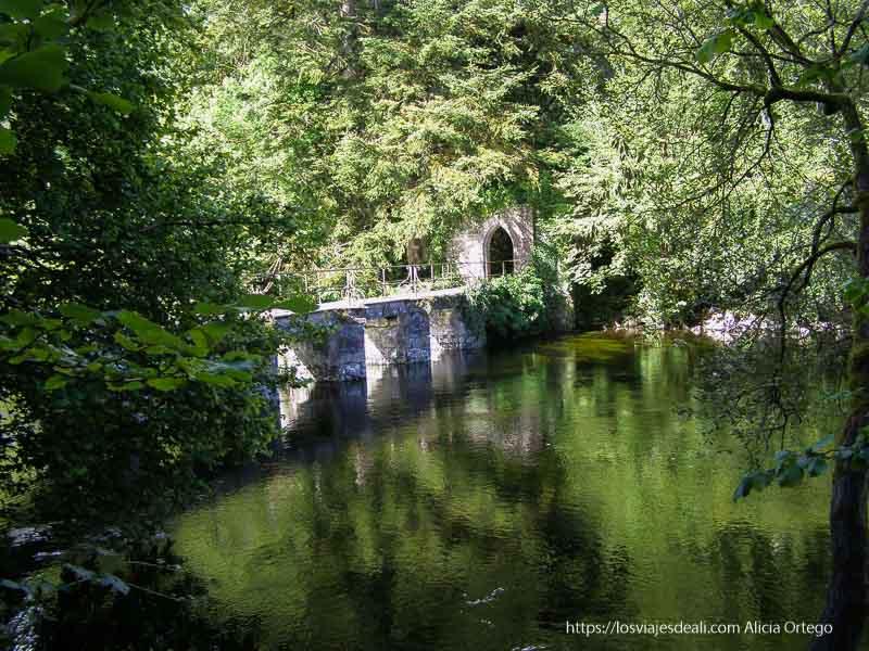 puente de piedra sobre el río de Cong rodeado de grandes árboles verdes que se reflejan en el agua