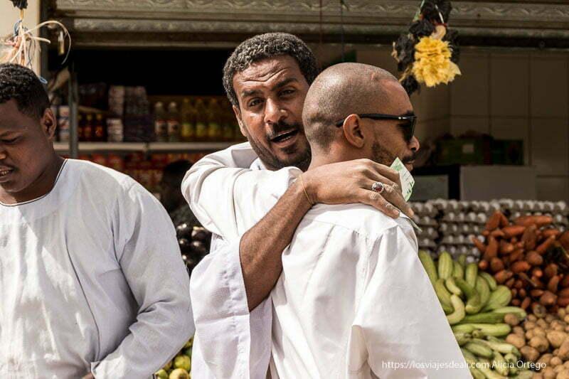 hombres del mercado de dongola posan abrazados y uno mira hacia mi justo cuando hago la foto gentes de sudán