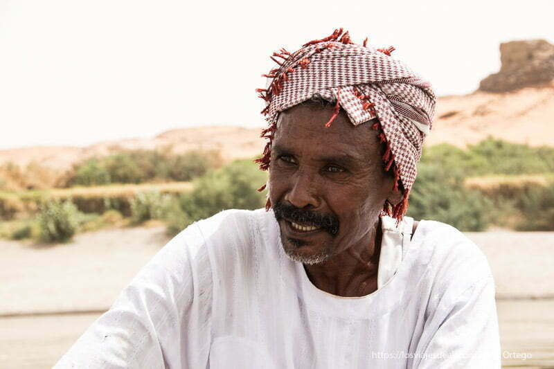 pescador del nilo con turbante rojo y blanco en la cabeza y sonriente gentes de sudán