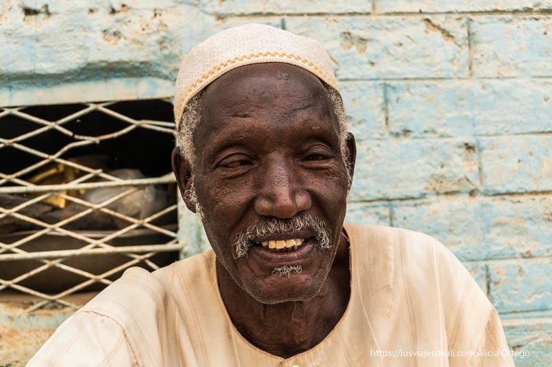 hombre del mercado de karima con pelo cano y gorrito bordado sonriendo gentes de sudán