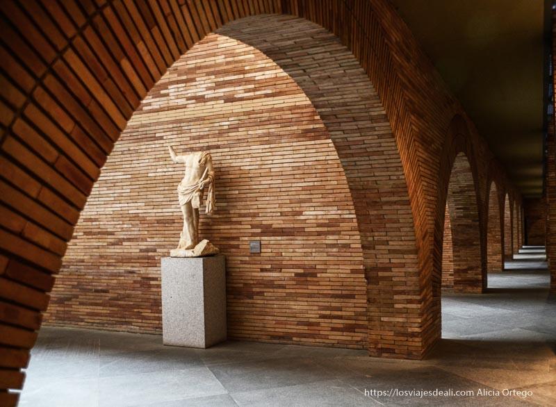 pasillos con paredes de ladrillos y arcos y una estatua romana museo de arte romano de mérida