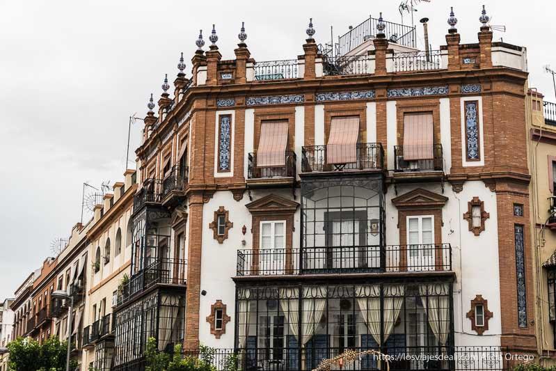 fachada de ladrillo, azulejos y balcones acristalados de triana planes en sevilla