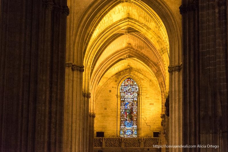 vidriera al fondo con arcos góticos en la catedral de sevilla