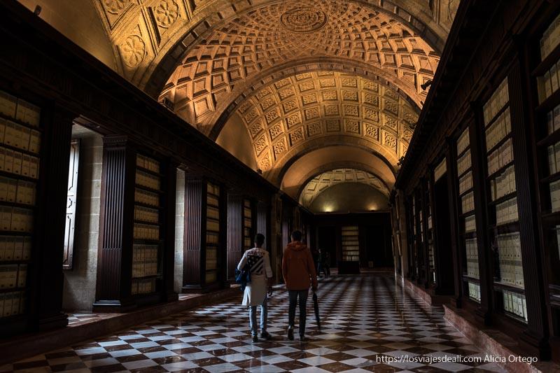 galería interior del archivo de indias con cajas llenas de legajos y suelo adamascado planes en sevilla