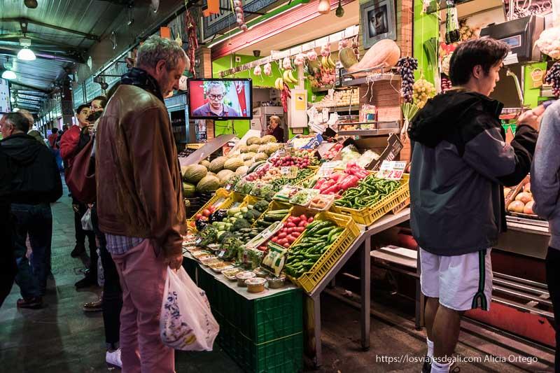 puesto de frutas con tele puesta y clientes esperando en mercado de triana planes en sevilla