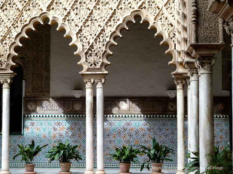 detalle de patio del alcázar con columnas de mármol y pared llena de azulejos planes en sevilla