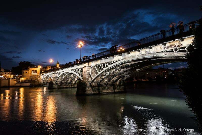 puente de triana por la noche iluminado con gente con paraguas planes en sevilla