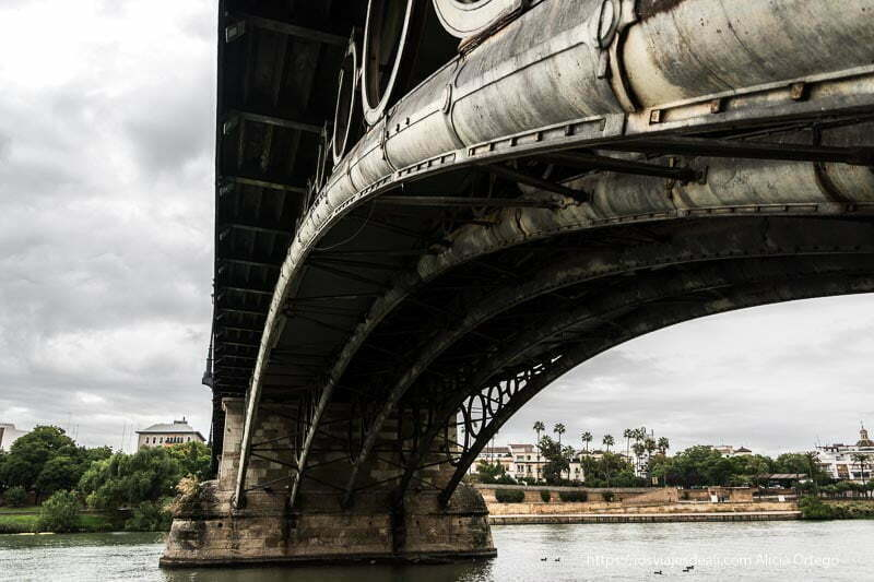 puente de triana desde abajo con cielo muy nublado planes en sevilla