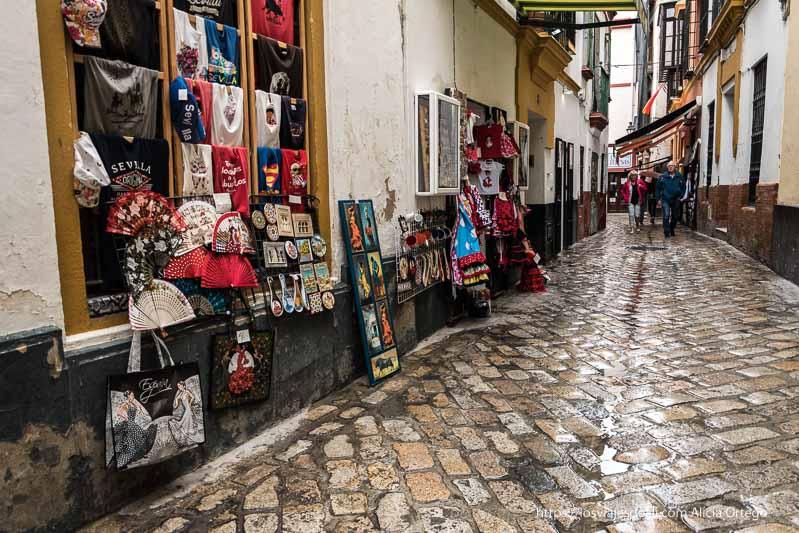 balle adoquinada del barrio de santa cruz con tienda de souvenirs en primer plano planes en sevilla