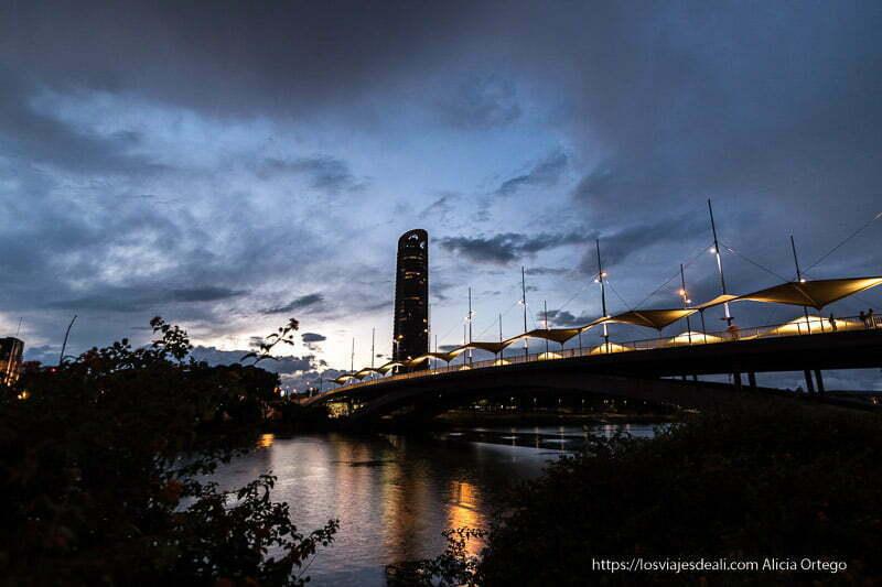 puente con torre sevilla y cielo nublado al atardecer planes en sevilla