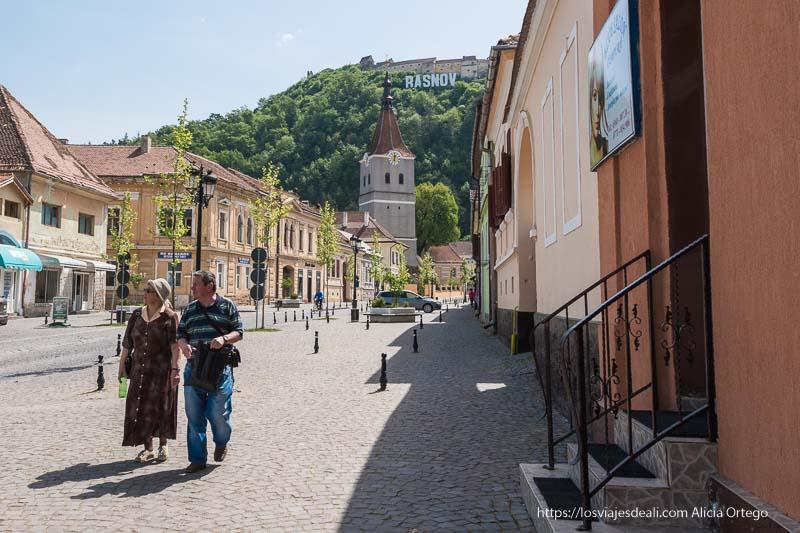 pareja paseando en calle principal de Rasnov con iglesia al fondo y ciudadela en lo alto de la montaña