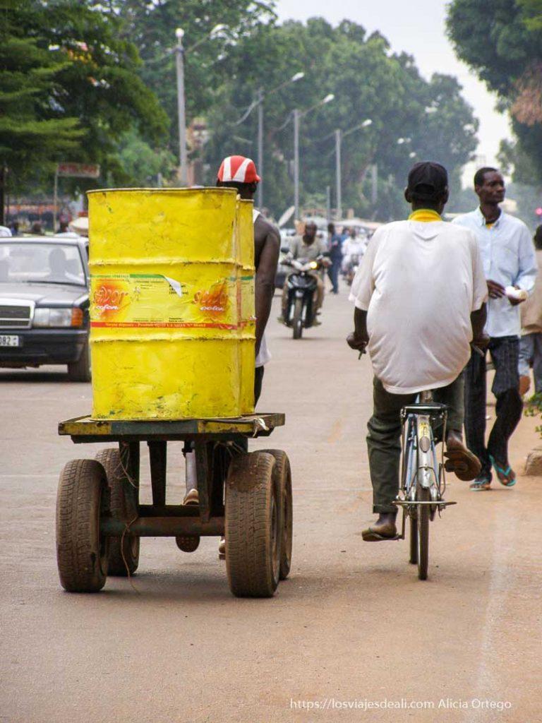 un carrito con dos bidones pintados de amarillo, motos, bicis... en ouagadogou