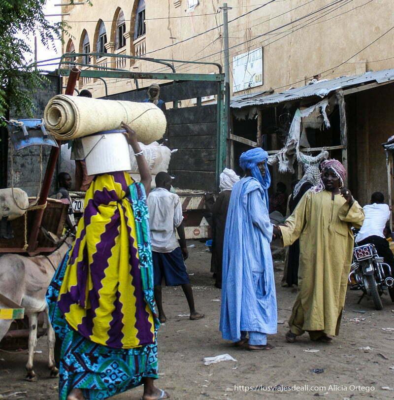 mercado de gao con un tuareg vestido de azul y una mujer que pasa con cosas en la cabeza