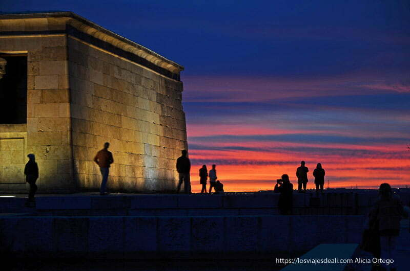 siluetas de gente al lado del templo de debod con cielo azul y rojo