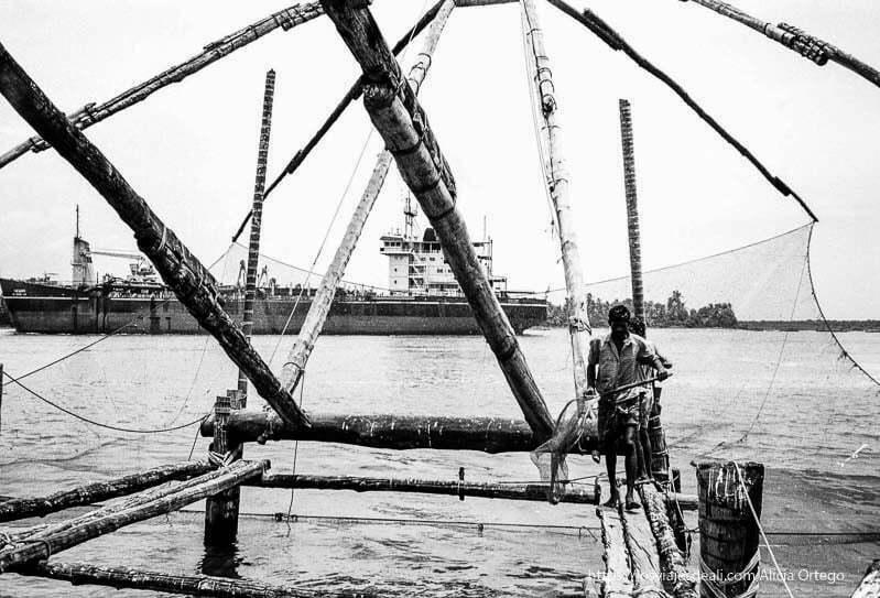 hombres andando por los palos de las redes chinas de kerala y un carguero al fondo