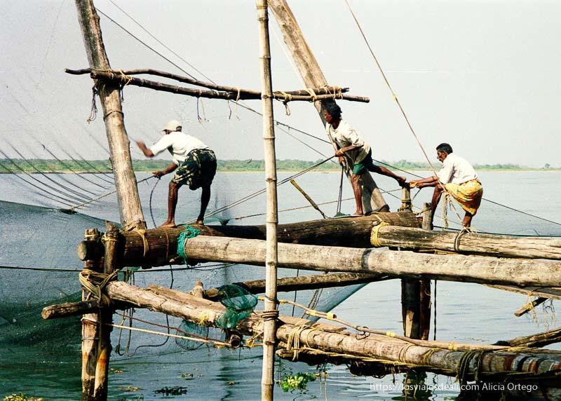 hombres faenando en las redes de pesca chinas de kerala