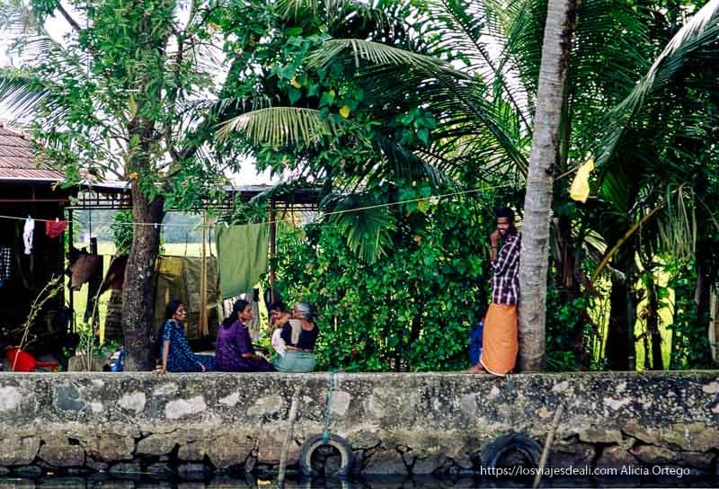 una familia sentada en la orilla de un backwater de kerala