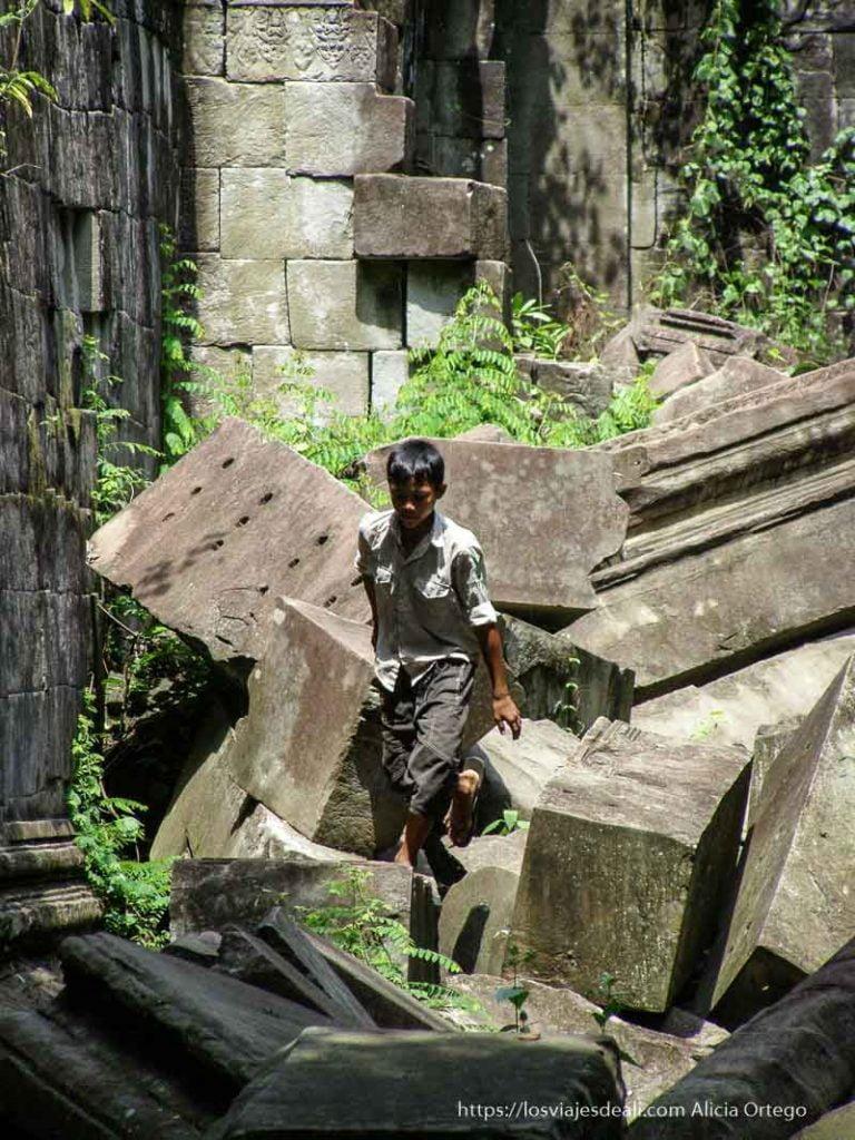 niño andando entre grandes bloques de piedra en beng mealea