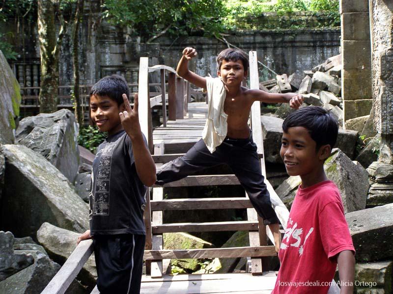 tres chicos camboyanos puestos en triángulo en las ruinas de beng mealea