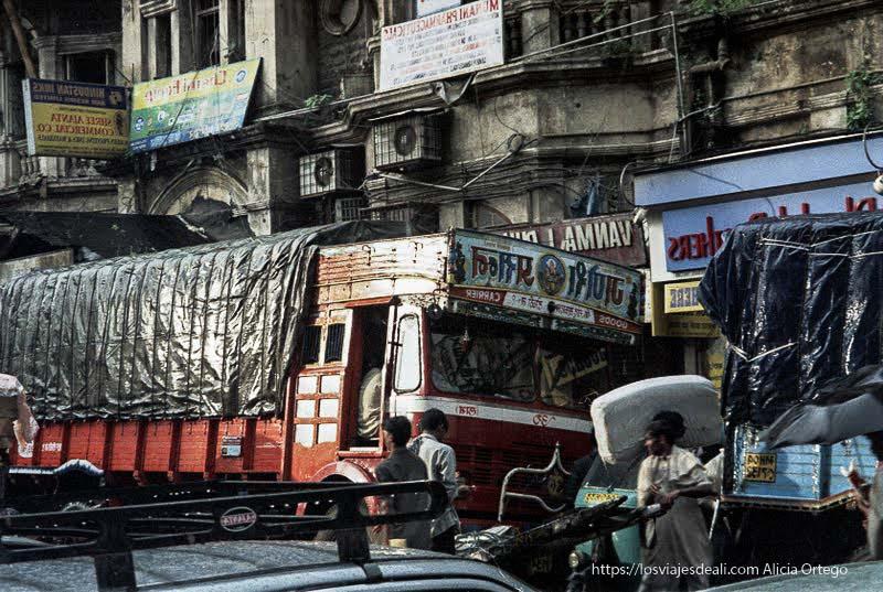 calle llena de camiones y hombres llevando cosas entre el tráfico en bombay