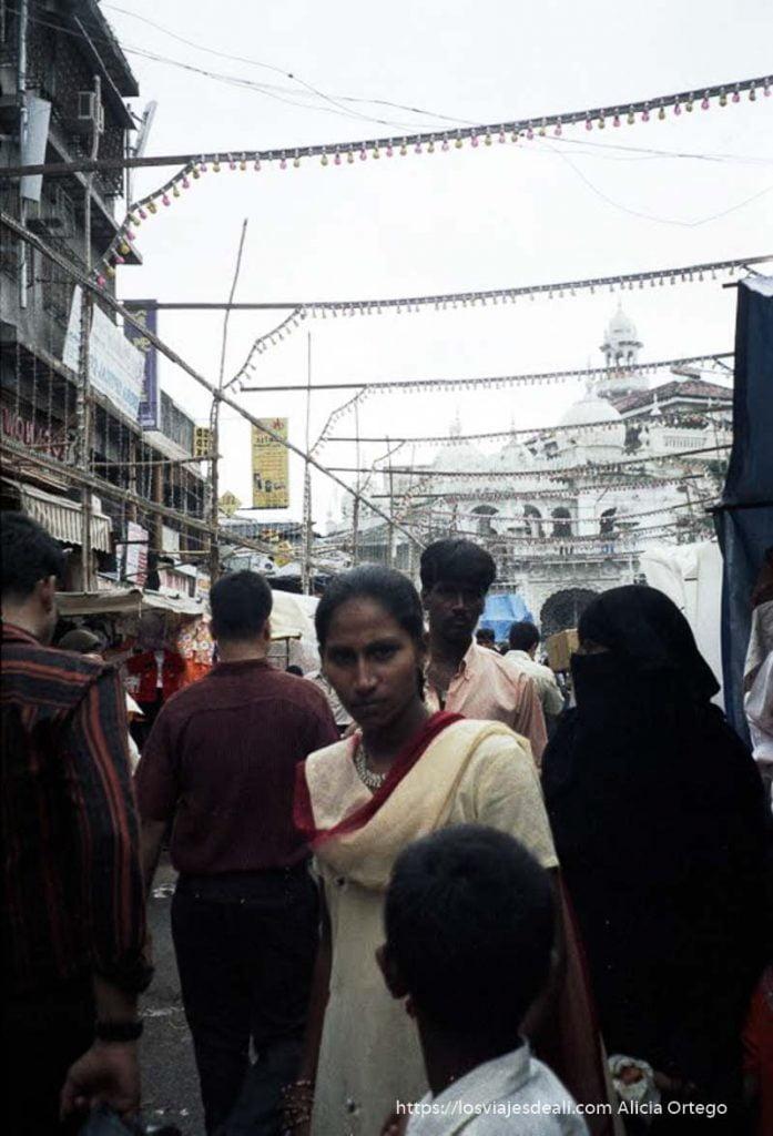 gente andando con mezquita detrás en bombay