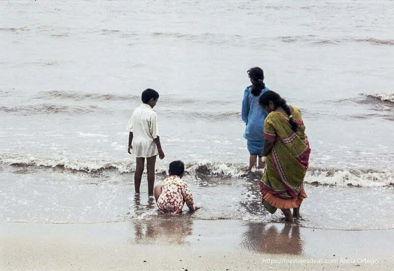 mujeres con sari y niños en la orilla de la playa de bombay