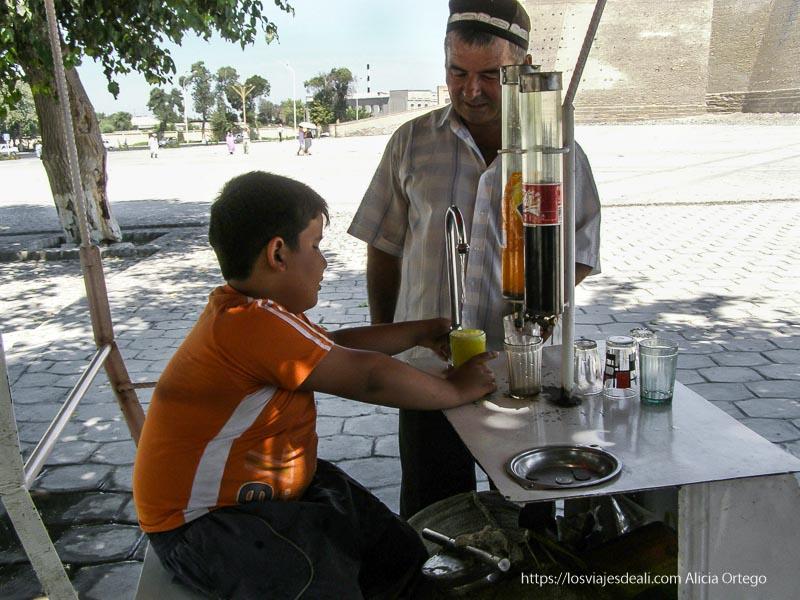 niño vendiendo coca cola y fanta naranja mezclando con agua en bukhara