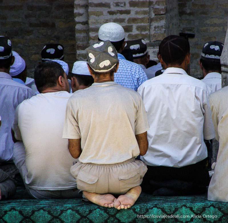 hombres de espaldas con gorritos bordados rezando en la mezquita de bukhara