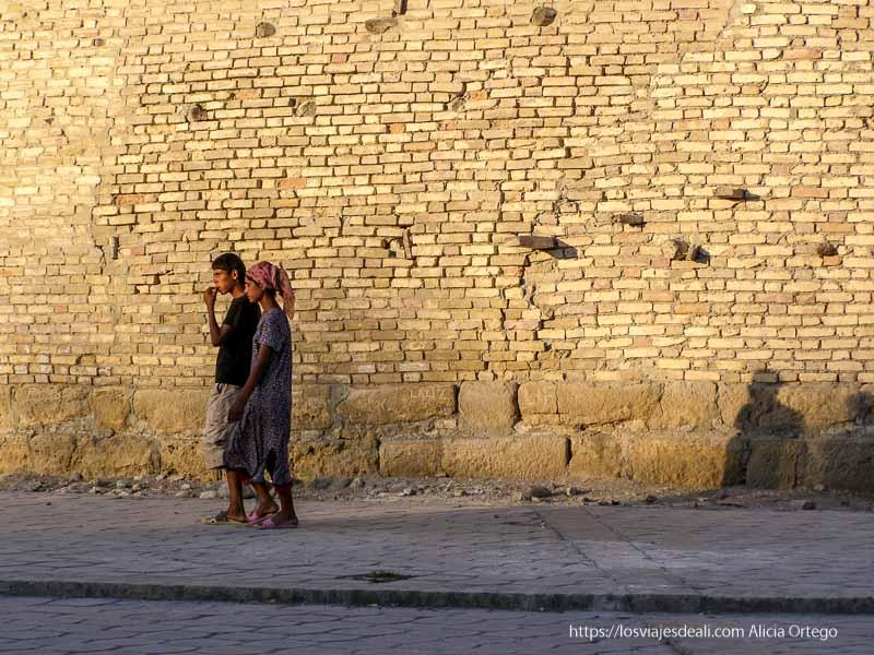 pareja joven de uzbekos andando junto a la muralla con luz de atardecer en bukhara