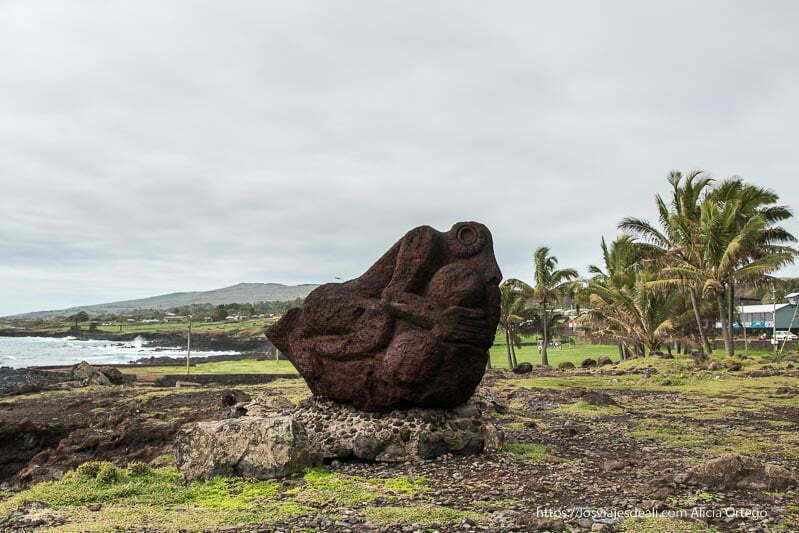 escultura en piedra roja con palmeras al fondo cómo es viajar a Isla de Pascua