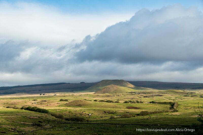 paisaje verde con cráteres de volcanes y nubes cómo es viajar a Isla de Pascua