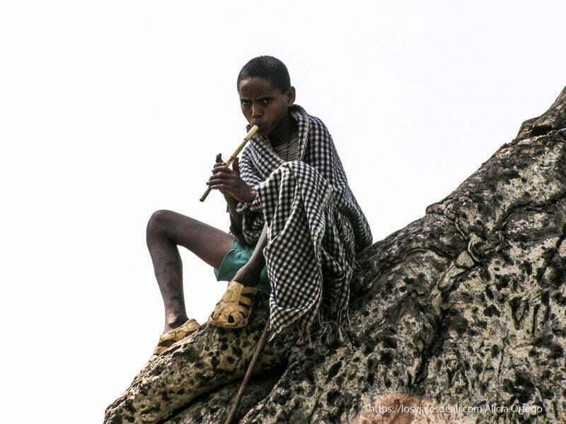 niño sobre tronco de árbol con manta a cuadros tocando una flauta