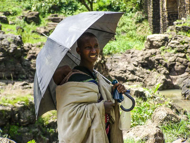 mujer con niño a la espalda protegiéndose con gran paraguas negro cataratas del nilo azul