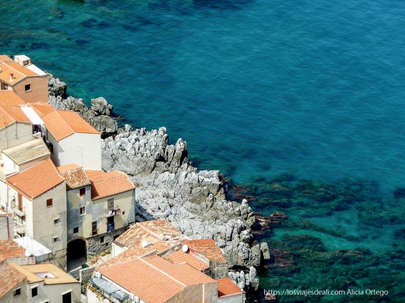 orilla rocosa y casas junto al mar en cefalú