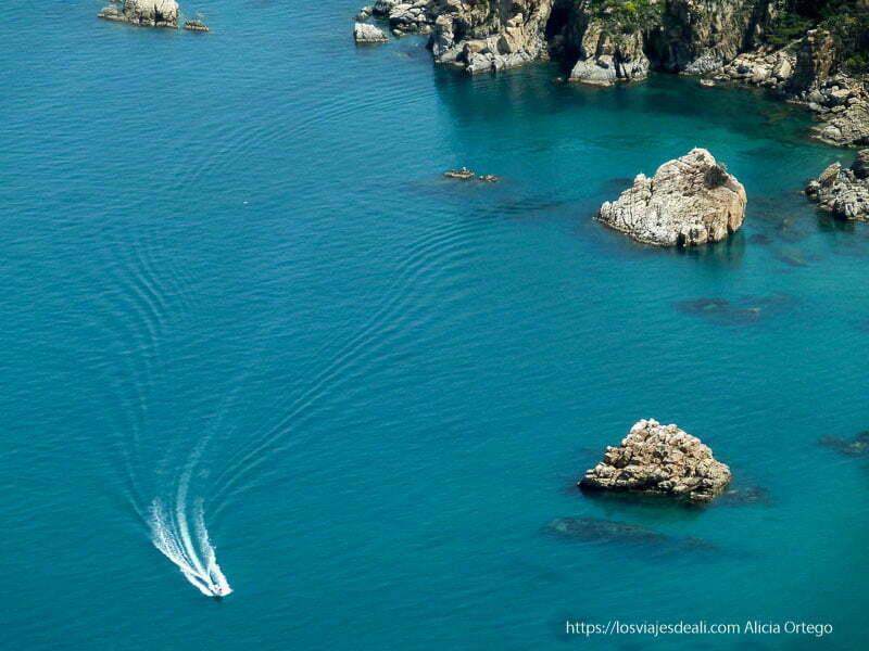 lancha motora surcando el mar y costa rocosa cefalú
