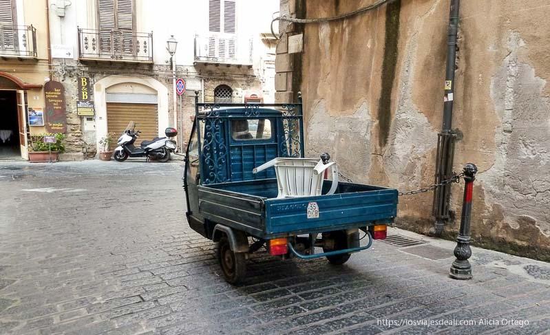 motocarro llevando silla de plástico en calles de cefalú