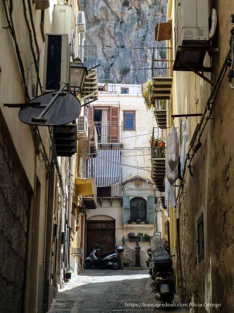 calle estrecha de cefalú con motos aparcadas, altar de virgen al fondo y la rocca
