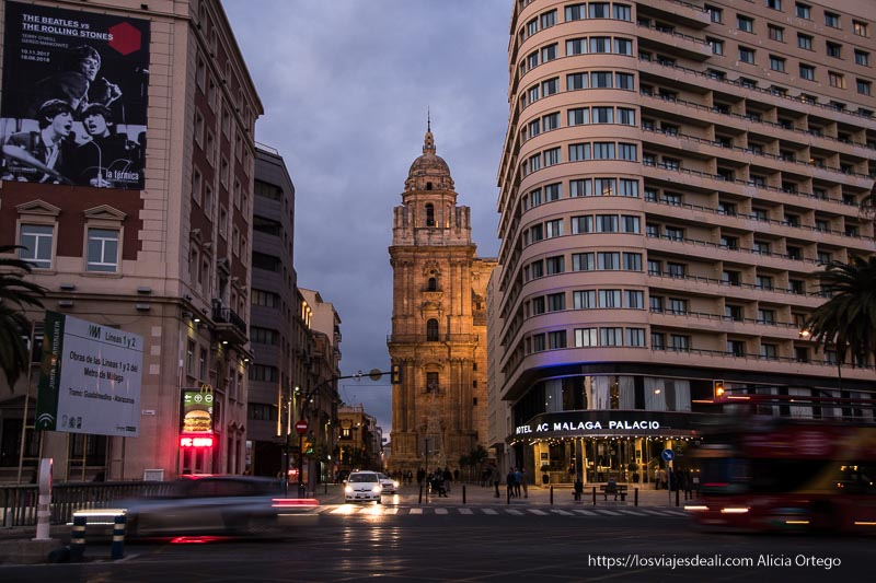 iglesia iluminada al fondo entre edificios modernos centro de málaga